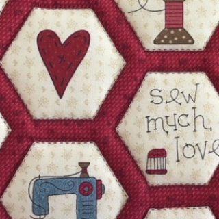 Rot-weißes Patchwork-Muster mit Symbolen wie Herz Garn und Nähmaschine