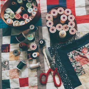 Schüssel mit Garnen und Garnrollen sowie Schere auf Patchwork-Decke